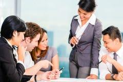 Hommes d'affaires asiatiques ayant la réunion dans le bureau Photo stock