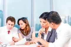 Hommes d'affaires asiatiques ayant la réunion dans le bureau Image stock