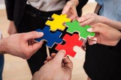 Hommes d'affaires assemblant le puzzle denteux Photos libres de droits