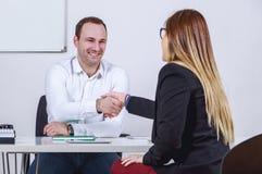Hommes d'affaires assis et femme d'affaires se serrant la main Photographie stock libre de droits