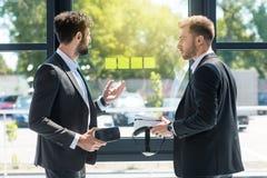 Hommes d'affaires avec des casques de réalité virtuelle dans des mains discutant le projet Photographie stock