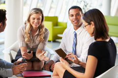 Hommes d'affaires avec la tablette de Digitals ayant le contact dans le bureau Images libres de droits