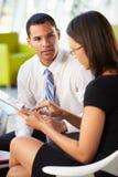 Hommes d'affaires avec la tablette de Digitals ayant se réunir interne photographie stock