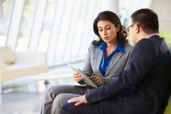 Hommes d'affaires avec la tablette de Digitals se reposant dans le bureau moderne image libre de droits