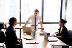 Hommes d'affaires avec le chef discutant ensemble dans la salle de conférence Image stock