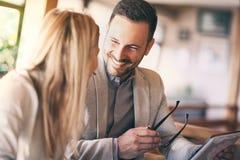 Hommes d'affaires avec le comprimé parlant en café ensoleillé photographie stock