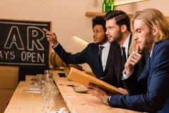 Hommes d'affaires avec le menu dans la barre Photo stock