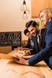 Hommes d'affaires avec le menu dans la barre Images stock