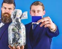 Hommes d'affaires avec le pot plein de l'argent liquide et de la carte de crédit, fond bleu, fin, l'espace de copie Banquier, dir photographie stock