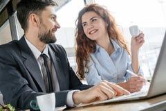 Hommes d'affaires ayant le déjeuner d'affaires à l'homme s'asseyant de restaurant dactylographiant sur l'ordinateur portable tand photographie stock