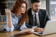 Hommes d'affaires ayant le déjeuner d'affaires à travailler se reposant de restaurant sur l'ordinateur portable tenant des docume image stock