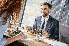 Hommes d'affaires ayant le déjeuner d'affaires au restaurant se reposant mangeant de la salade discutant le travail joyeux image libre de droits