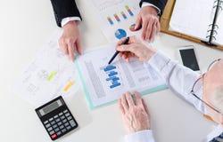 Hommes d'affaires ayant une discussion au sujet de rapport financier Photographie stock libre de droits