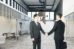 Hommes d'affaires caucasiens se serrant la main photos stock