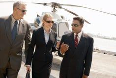 Hommes d'affaires communiquant avec l'hélicoptère à l'arrière-plan Photographie stock