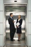 Hommes d'affaires communiquant dans l'ascenseur Images stock