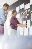 Hommes d'affaires créatifs discutant au-dessus du document sur le mur dans le bureau Image stock