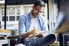 Hommes d'affaires dans la chemise bleue travaillant dur dans le matin se reposant en café Image libre de droits