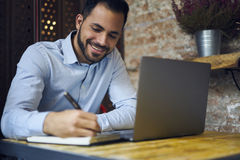 Hommes d'affaires dans la chemise bleue utilisant l'ordinateur portable moderne et wifi dans l'espace coworking Images stock
