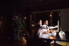 Hommes d'affaires dans le bureau la nuit fonctionnant tard Photos libres de droits
