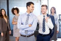 Hommes d'affaires de sourire se tenant ensemble dans l'avant et les femmes d'affaires se tenant à l'arrière-plan Photos libres de droits