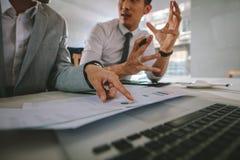 Hommes d'affaires discutant au-dessus d'une certaine analyse statistique photos libres de droits