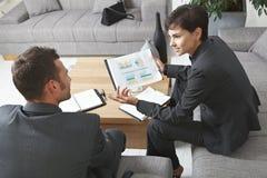 Hommes d'affaires discutant des diagrammes Photos stock