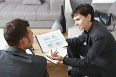 Hommes d'affaires discutant des diagrammes Images stock