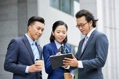 Hommes d'affaires discutant le projet en ligne sur le PC de comprimé photographie stock