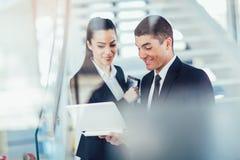 Hommes d'affaires discutant tout en à l'aide de l'ordinateur portable photos stock