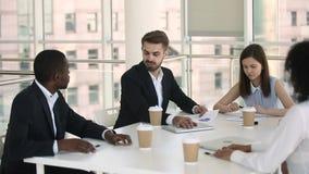 Hommes d'affaires divers dans le tenue de soirée négociant pendant se réunir dans la salle de réunion clips vidéos