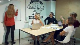 Hommes d'affaires divers se réunissant faisant un brainstorm l'équipe Fille dans la chemise rouge présentant la stratégie réussie banque de vidéos