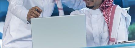 Hommes d'affaires du Moyen-Orient au bureau travaillant sur un ordinateur portable image stock