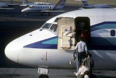 Hommes d'affaires embarquant l'avion à réaction de banlieusard Image stock