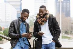 Hommes d'affaires employant le mobile dans la rue Image stock
