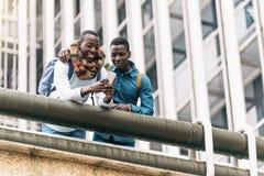 Hommes d'affaires employant le mobile dans la rue Photographie stock libre de droits