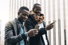 Hommes d'affaires employant le mobile dans la rue Photo stock