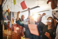 Hommes d'affaires encourageants faisant un brainstorm avec les notes collantes dans de image libre de droits