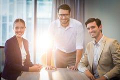 Hommes d'affaires et femme d'affaires s'asseyant à leur bureau photos stock