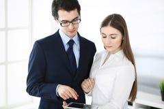Hommes d'affaires et femme ? l'aide de la tablette dans le bureau moderne Coll?gues ou chefs d'entreprise sur le lieu de travail  photo stock