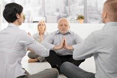 Hommes d'affaires exerçant le yoga dans le bureau Photographie stock