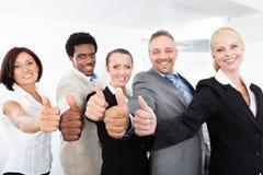 Hommes d'affaires faisant des gestes le pouce vers le haut du signe Image stock
