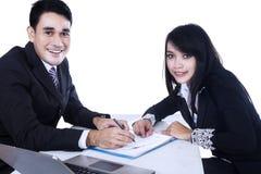 Hommes d'affaires heureux signant le contrat d'affaires Photo stock