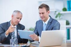 Hommes d'affaires heureux travaillant ensemble sur le comprimé numérique Photos stock