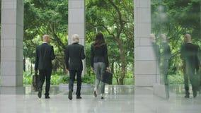 Hommes d'affaires intellectuels marchant sortant le bâtiment moderne