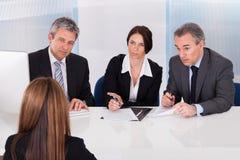 Hommes d'affaires interviewant la femme Photo stock