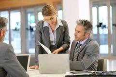 Hommes d'affaires lors d'une réunion de travail sur l'ordinateur portable images stock