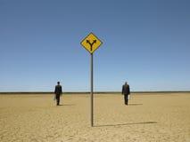 Hommes d'affaires marchant après le panneau routier dans le désert Images libres de droits