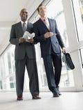 Hommes d'affaires marchant dans le couloir de bureau Image libre de droits
