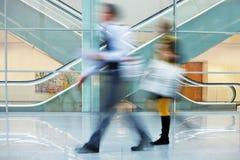 Hommes d'affaires marchant rapidement avec le bagage vers le bas Hall dans le bureau Images stock